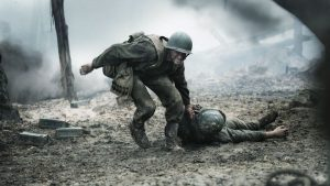 Doss pulling a man from the battlefield. Image from HACKSAW RIDGE.
