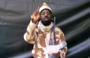Boko Haram Maggot-In-Chief Abukakar Shekau Note funny hat pilfered from bottom of Ghadafi's closet. Image from Voice of America