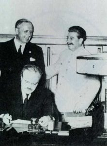 German Ambassador Joachim von Ribbentrop, Soviet Dictator Josef Stalin, and Soviet Foreign Minister Vyacheslav Molotov signing Ribbentrop-Molotov Pact of NAZI-Soviet non-agression, Poland, 1939. Image public domain, wikimedia commons.