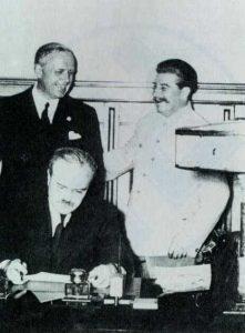 German Ambassador Joachim von Ribbentrop, Soviet Dictator Josef Stalin, and Soviet Foreign Minister Vyacheslav Molotov signing Ribbentrop-Molotov Pact of NAZI-Soviet non-agression, Poland, 1939. Image public domain, wikimedia commons.