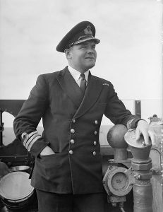 Commander Donald MacIntyre RN on the bridge of HMS HESPERUS. Image at Imperial War Museum, public domain.