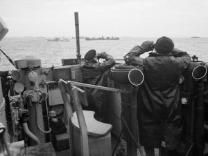 Officers watching for submarines on the bridge of a destroyer that was escorting a large convoy. Image at Imperial War Museum, public domain.